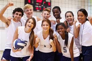 Happy co-ed volleyball team grouped with coach for a picture